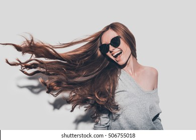 Hair like fire. Attractive young smiling woman in sunglasses and with tousled hair looking away while standing against grey background