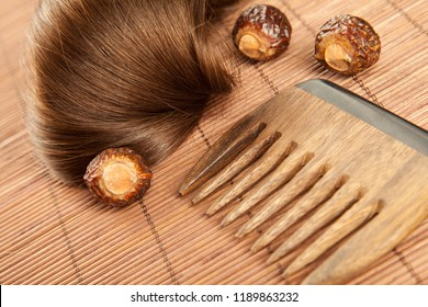 Hair lock, soapnuts and wooden comb on bamboo background; haircare concept