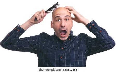 Hair loss concept. Shocked bald man with a comb. Isolated on white