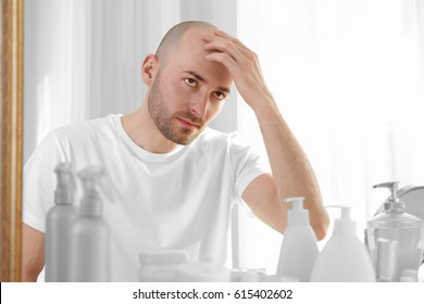 Hair loss concept. Young man looking at mirror