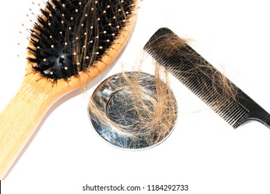 Hair loss on washbasin. Long brown hair with black comb and wood brush on white basin in the bathroom. Healthcare concept