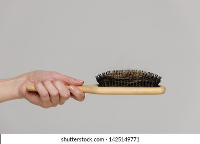 Hair loss problem, postpartum period, menstrual or endocrine disorder, hormonal disbalance, menopause, stress concept. Close up of woman hand holding comb brush with lost hair, side view, free space.
