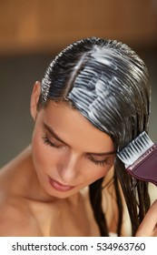 Hair Masking. Young Woman With Brush In Hand Applying Natural Mask On Long Healthy Hair. Beautiful Girl Spreading Conditioner Along Wet Hair. Health And Beauty. High Resolution Image