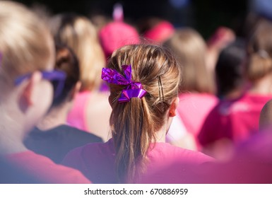 Hair pony tail with pink ribbon as a symbol for fighting cancer. Surrounded by ladies wearing pink all raising money to fight cancer. With a vignette.