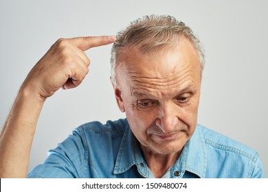 Hair problems. Pensioner points a finger at gray hair. The old man is balding. On a white background in a blue shirt