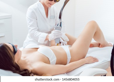 Hair removal in bikini zone using a laser device on young woman in cosmetic treatment