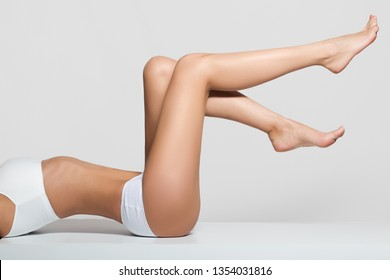 Hair removal concept. sexy long legs. Young female touching her hairless smooth soft and silky skin. Beauty body care concept