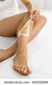 Hair Removal. Long Woman Legs With Wax Strip On. Closeup Of Female Depilates Her Sexy Slender Long Legs, Removing Hair For Perfect Smooth And Silky Skin. Depilation, Beauty Body Care Concept