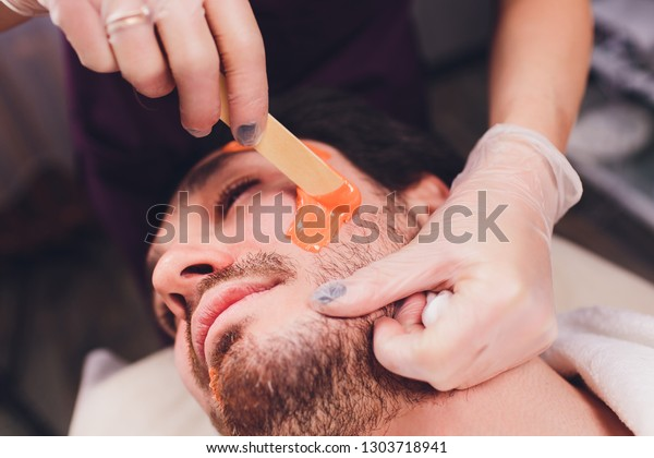 Hair removal. Man's face sugaring epilations beard trimming, yellow color, in cosmetology on the couch.