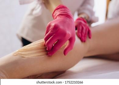 Hair removal at spa studio. Woman legs wax with shugaring. Hot sugar.