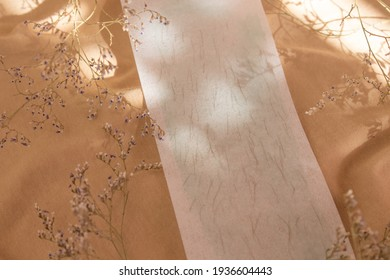 Hair removal wax strip at home. used strip for depilation with legs on a beige natural fabric with fresh flowers around and a beautiful shadow. Stele hair removal concept.