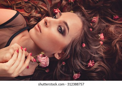 hair with roses expand on the fabric colored Marsala. top view image of a girl with long curly hair.