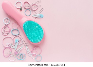 Hair scrunchies and hairpins, hairbrush on pink background, beauty concept. flat lay. free space for text