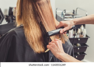 Hair straightening at beauty salon. Hairdresser making a hairstyle for client with a hair iron