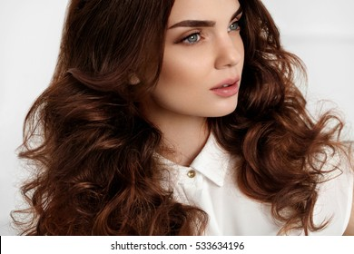 Hair Style. Beautiful Woman With Healthy Long Wavy Curly Hair And Gorgeous Face Makeup. Portrait Of Brunette Girl Model With Fashion Hairstyle, Brown Hair Color And Perfect Curls. Beauty. High Quality