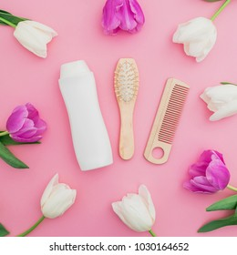 Hair styling concept with shampoo, combs and tulips flowers on pink background. Flat lay, top view