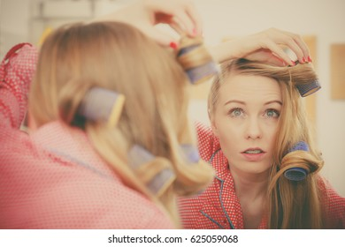 Hair styling at home concept. Woman wearing pajamas curling her hair using rollers in bathroom