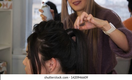 Hair stylist apply fixing hairspray. Fishbone braid. Image completion. Final touch. Hairdressing services. Beauty industry