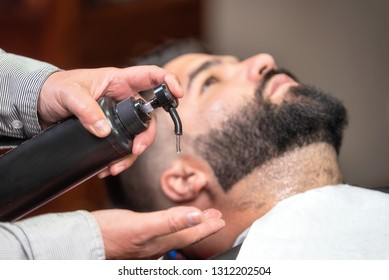 Hair stylist applying after shaving lotion at barber shop .