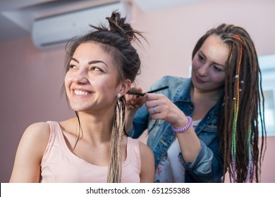 A hair stylist braids Zizi cornrows to a young and beautiful girl. dreadlocks plait