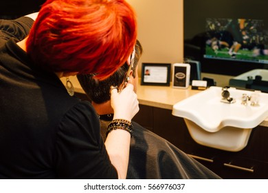 Hair stylist cuts man's hair while he watches football on television in a luxurious, modern barbershop.