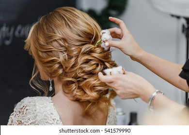 Hair stylist or florist makes the bride a wedding hairstyle with fresh cotton flowers - Shutterstock ID 541579990