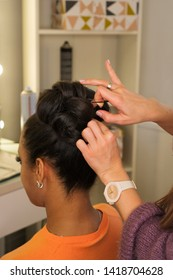 Hair stylist hands form high hairstyle on head of young African American. Pinning curls with hairpins and hair slide. Master class on creating high evening hairstyle. Training. Public lesson