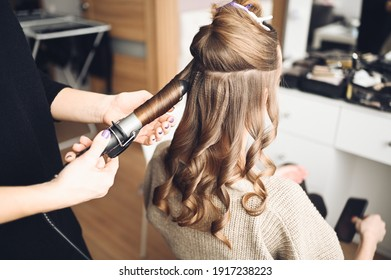 Hair stylist prepares woman makes curls hairstyle with curling iron. Long light brown natural hair