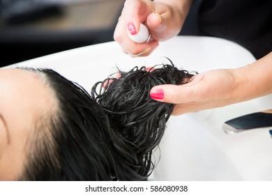 Hair stylist putting repairing mask on woman's hair in beauty salon. Hair wash shampoo