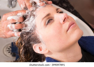 Hair stylist shampooing hair of a female customer