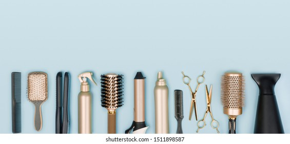 Hair stylist tools arranged in a line on blue background