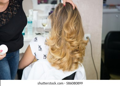 Hair stylist using hairspray after blow drying the hair of a blond woman in a beauty salon