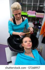 hair stylist washing woman hair in salon pool