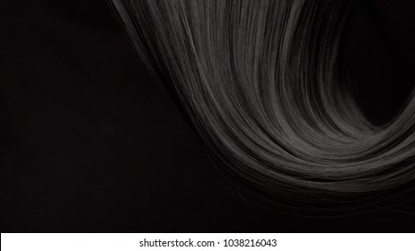 Hair texture background, no person. Black shiny hair curl on blsck