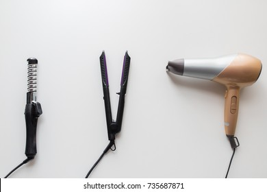 hair tools, beauty and hairdressing concept - hairdryer, hot styler and curling iron or tongs on white background