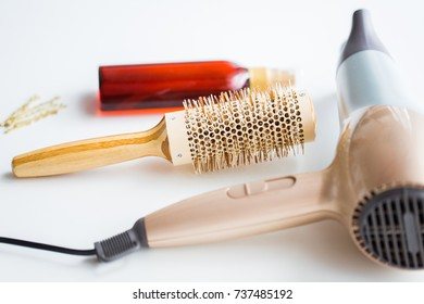 hair tools, beauty and hairdressing concept - hairdryer, brush, hot styling spay and pins on white background
