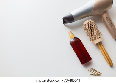 hair tools, beauty and hairdressing concept - hairdryer, brush, hot styling spray and pins on white background