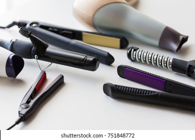 hair tools, beauty and hairdressing concept - hot styling and curling irons with hairdryers on white background