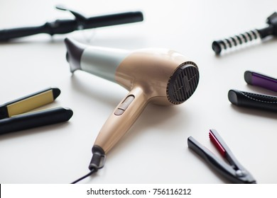 hair tools, beauty and hairdressing concept - hairdryer, hot styling and curling irons on white background
