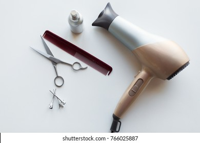 hair tools, beauty and hairdressing concept - hairdryer, scissors, comb and styling spray on white background