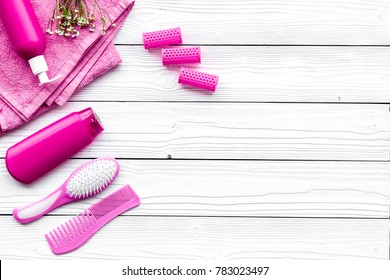 Hair washing and styling tools. Comb, shampoo, hairspray, curlers on white wooden background top view copyspace