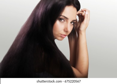 Hair. Young girl with beautiful dark long hair. Well-groomed hairstyle. Beauty salon. The concept of beauty. On a gray background.
