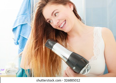 Haircare. Beautiful long haired woman drying hair in bathroom