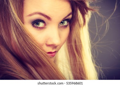 Haircare, beauty, hairstyling concept. Closeup portrait of young attractive blonde woman wearing dark t shirt having windblown beautiful long hair.