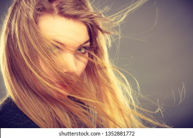 Haircare, beauty, hairstyling concept. Portrait of young attractive blonde woman wearing dark t shirt having windblown beautiful long hair on her face.
