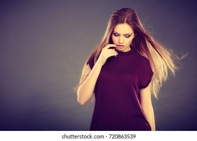 Haircare, beauty, hairstyling concept. Portrait of young attractive brunette woman wearing dark tshirt having windblown beautiful long brown hair.