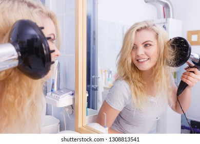 Haircare. Beauty long haired blonde woman drying hair in bathroom. Smiling girl blowing wind on wet head using hairdryer, doing curls with diffuser nozzle.
