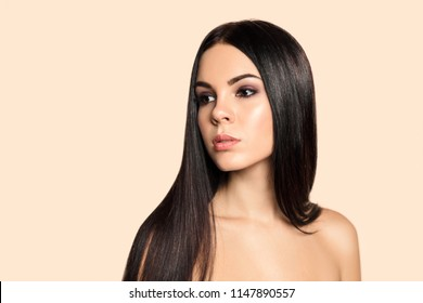Haircare. Beauty portrait of young brunette woman with perfect healthy  skin and smooth hait. Attractive model with natural professional make up. Hairdress salon and cosmetics concept
