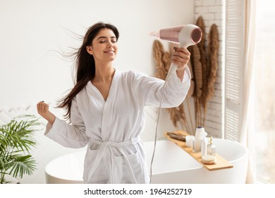 Haircare. Brunette Woman Drying And Styling Hair With Hairdryer Making Hairstyle Standing In Modern Bathroom At Home. Happy Female Using Hair Dryer Enjoying Beauty Routine After Morning Shower