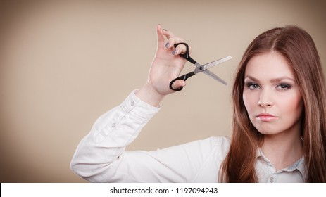 Haircare concept. Cutting and trimming. Young prefessional female barber hairstylist with scissors. Portrait of long haired girl prepared to styling hair.